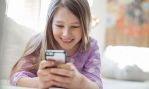 Young girl text messaging with mobile phone on sofa