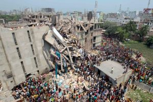 People and rescuers gather after an eight-story building housing several garment factories collapsed in Savar, near Dhaka, Bangladesh, Wednesday, April 24, 2013.